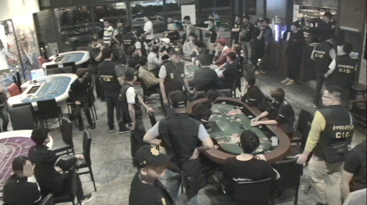 檢警前天深夜11時許再抄「RAISE遊戲主題餐廳」,男、女店員身著店內黑上衣、黑...