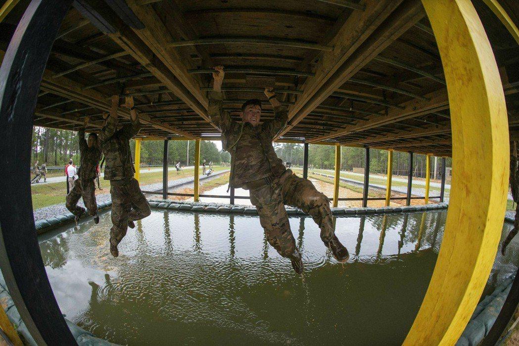 參賽者攀爬俗稱飛猴單槓(monkey bars)過河的畫面。 (美聯社)