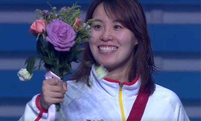 傅園慧在頒獎台上興奮地搖著花。圖擷自FINA粉絲專頁