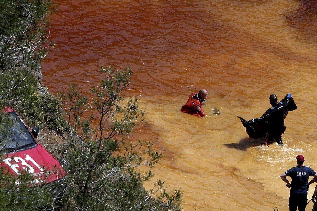 潛水員從湖中打撈起裝有被害屍體的行李提袋。 圖/美聯社