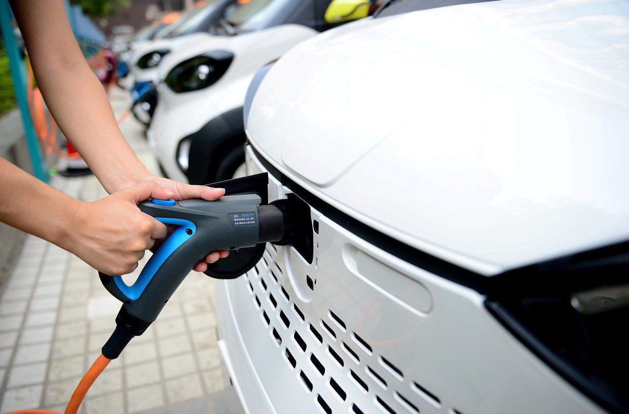 位於中國廣西柳州的一處充電站,一名員工正在為電動車充電。 路透