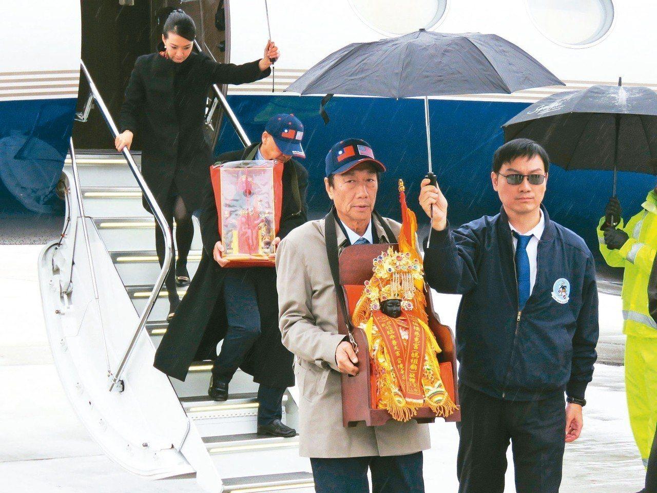 鴻海董事長郭台銘(右二)搭專機前往威州,抱著媽祖神像下機。 特派記者張加/攝影