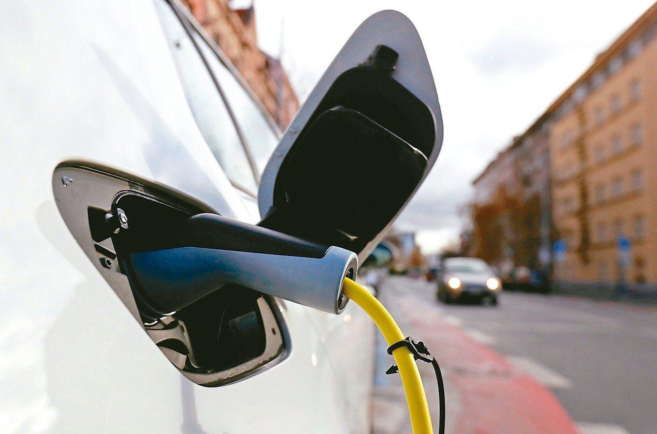 圖為電動車在路邊充電站充電畫面。 路透