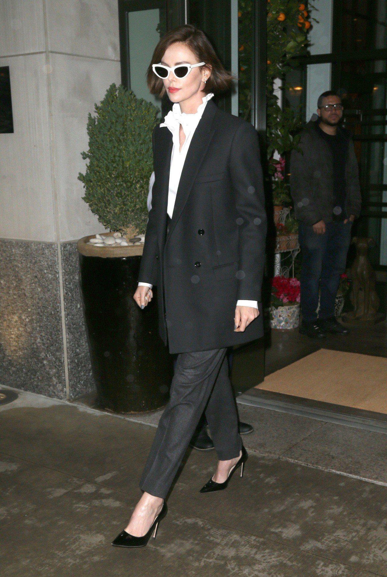 莎莉賽隆以荷葉領白襯衫和墨鏡巧搭CELINE西裝外套,整身穿搭很有層次感。圖/C...