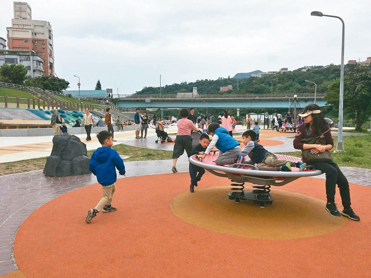 北市道南河濱公園共融式遊戲場有沙坑、鞦韆、滑梯,並結合無障礙設施概念,讓兒童盡情...