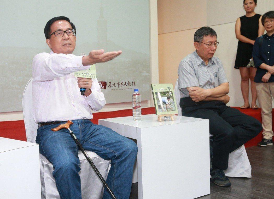 前總統陳水扁(左)昨在新書發表會上,伸出顫抖的手要在旁的台北市長柯文哲及媒體確認...