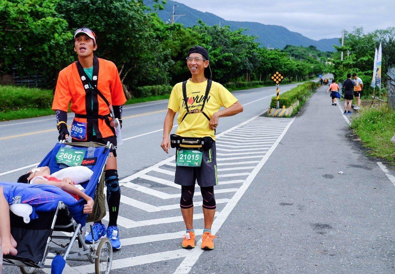 參加今天金剛馬拉松的跑友,主動幫小比媽陳嘉齡推娃娃車帶著魯夫小比往前跑。圖/東管...
