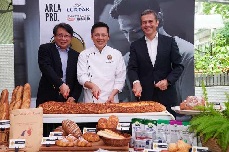 開幕當天,創辦人陳耀訓與來賓切下巨型「聲頌法國麵包」。圖/Yoshi Baker...