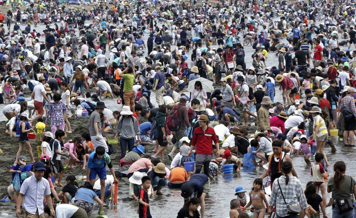 黃金週連假是日本旅遊觀光人潮旺季,圖為連假期間在橫濱附近沙灘人滿為患的遊客。 圖...