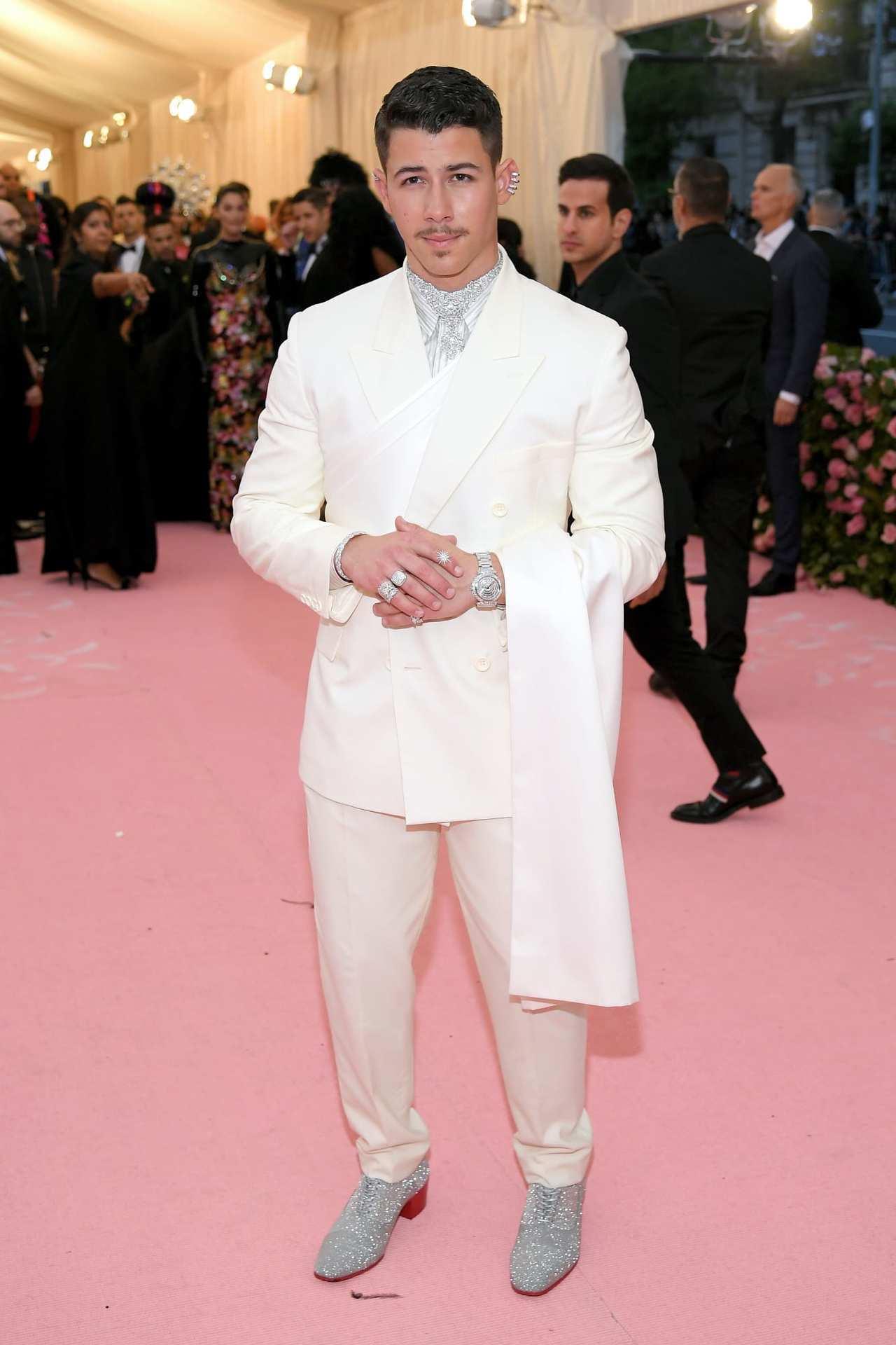 Nick Jonas穿戴了不少鑽戒、耳環和鑽表在身上,混搭了Dior的白色斜襟西...