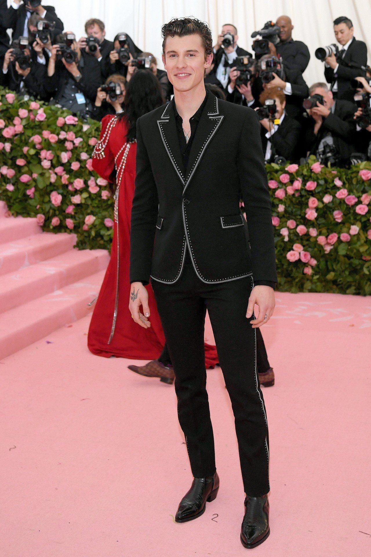 歌手Shawn Mendes身穿黑色帶有白色飾邊的西服,來自Saint Laur...