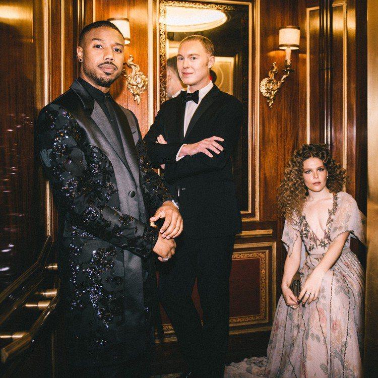 男星Michael B. Jordan(左一)的黑色綴飾亮片的大衣和長褲,則是由...