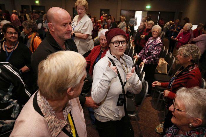 一名女子(中)用蛋襲擊澳洲總理莫里森後,比出勝利手勢。翻攝自澳洲廣播公司