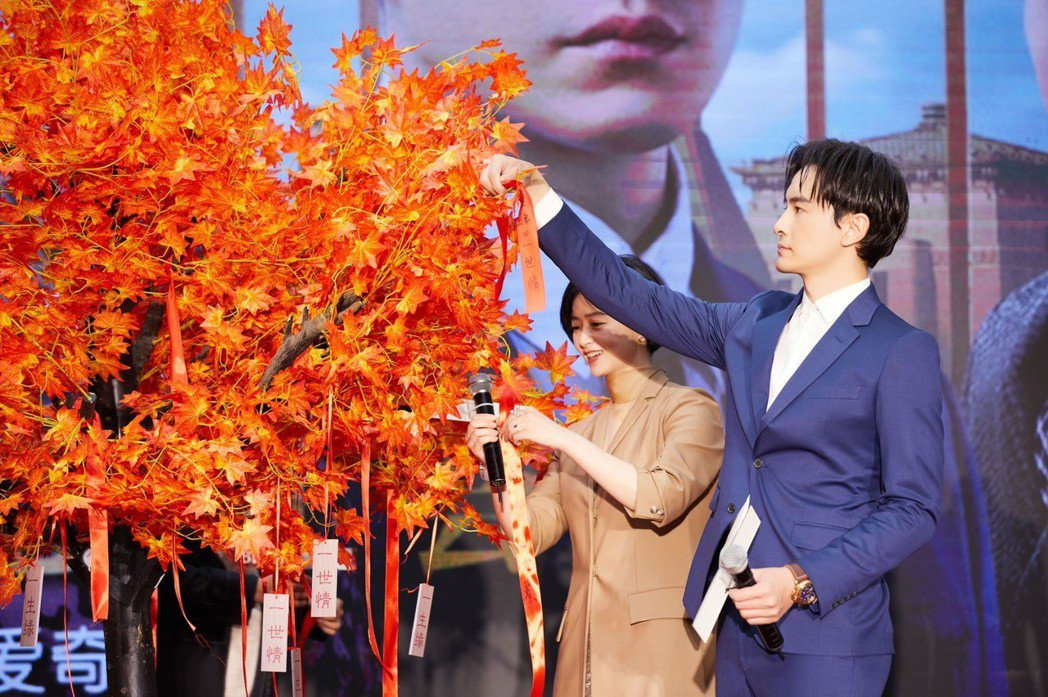 鄭元暢(右)、蔣欣綁紅絲帶在樹上,進行許願儀式。圖/M.I.E.最大國際提供