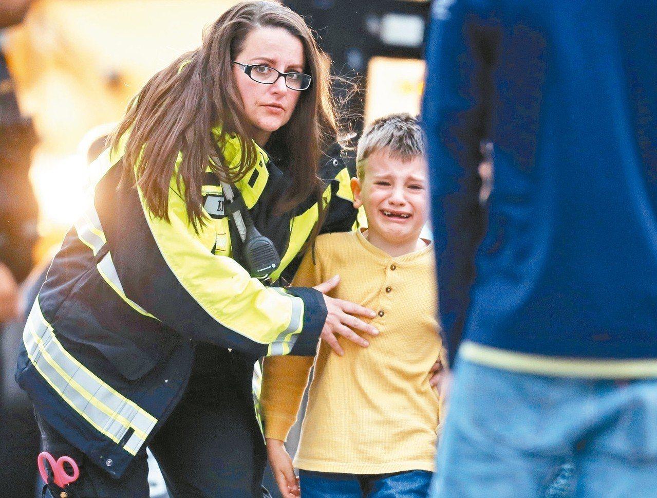 丹佛郊區中學7日爆發槍擊事件後,大批警消人員趕到現場,救護人員安撫受到驚嚇的學生...