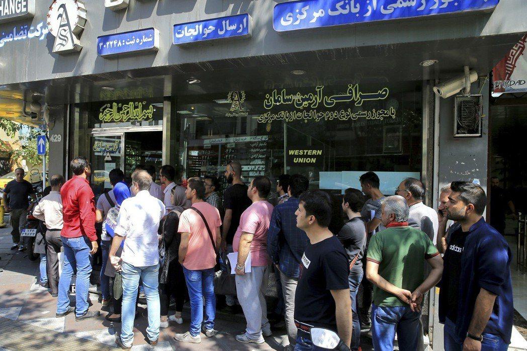 去年9月5日,大批擔心里亞爾貶勢的伊朗民眾在外匯兌換店前排隊兌換美元和歐元。 (...