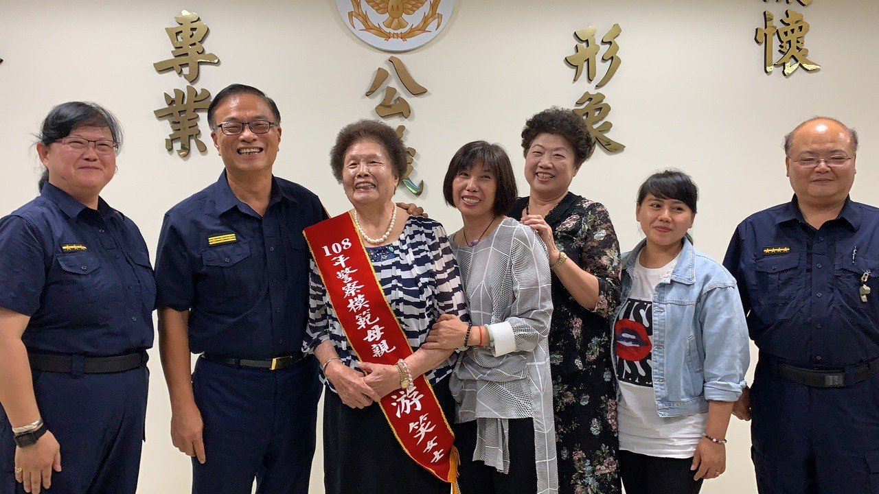 台南市警局長黃宗仁(左二)表揚獲全國警察模範母親的江游笑(右五),其育有十名子女...