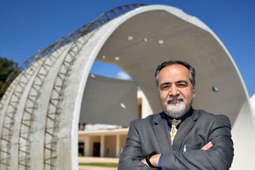 一名出席國際隧道會議的教授,與會場外展示的混凝土隧道結構合影。 (法新社)