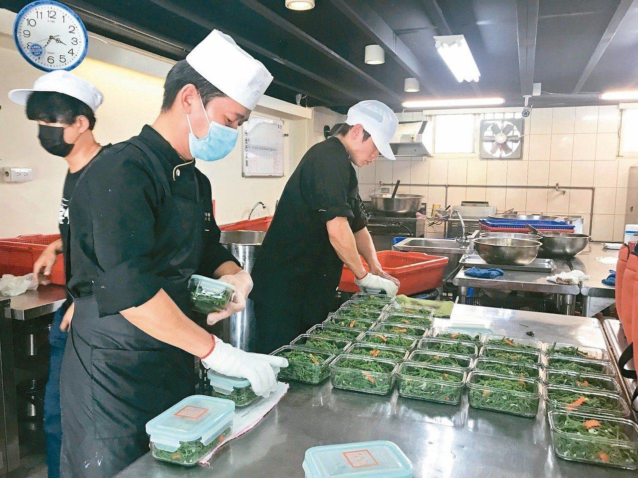 「宅夕食」員工們正忙著將剛製作完成的菜餚分裝到環保餐盒中。 記者郭政芬/攝影