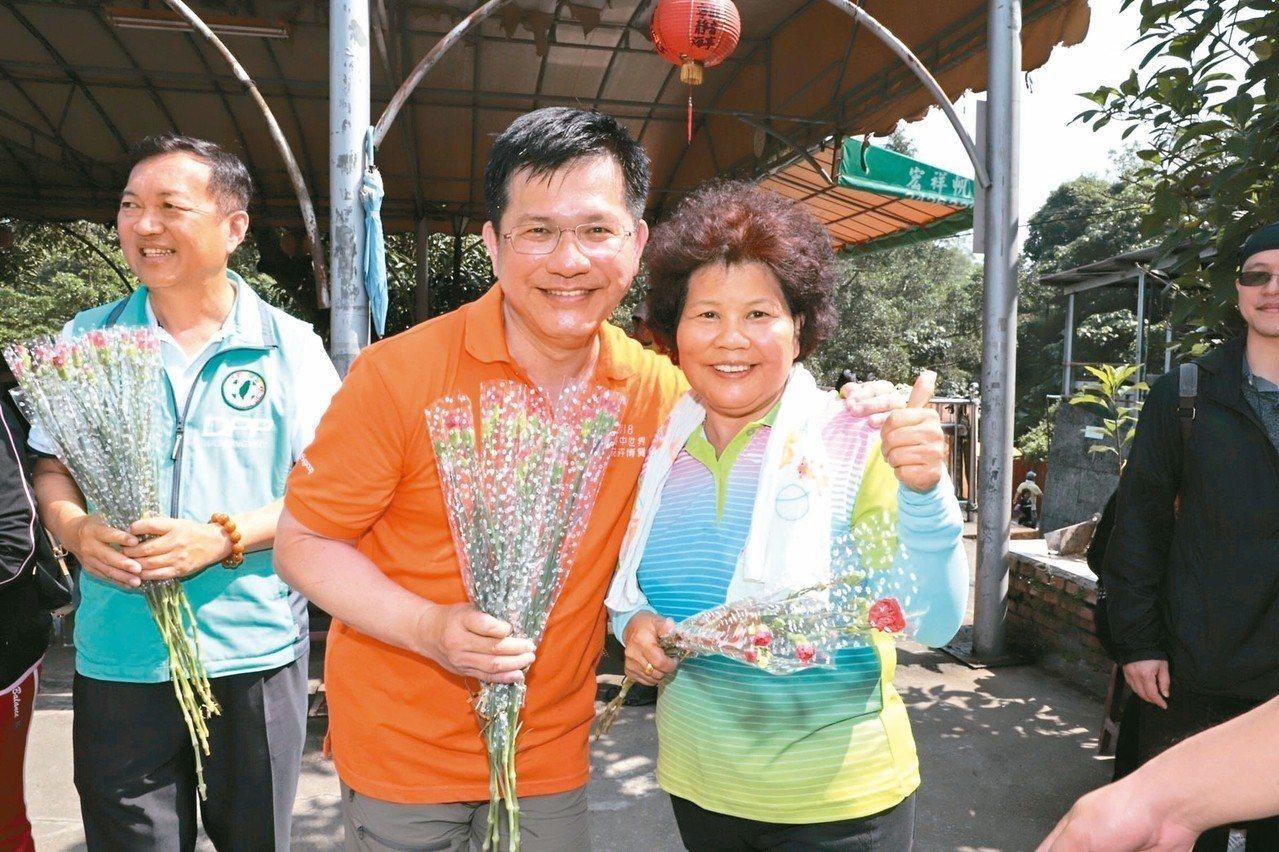 交通部長林佳龍(中)昨清晨在台中大坑步道,發送康乃馨給山友,他已連續11年在母親...