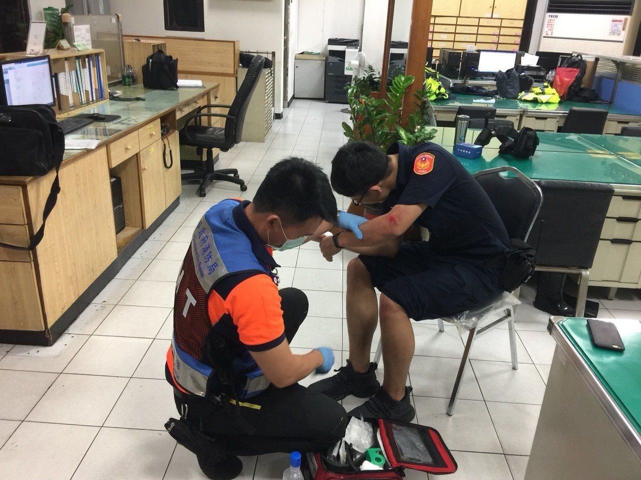 警員洪福臨追捕拒檢外籍移工,手腳擦傷,救護人員為他裹傷。記者黃宣翰/翻攝