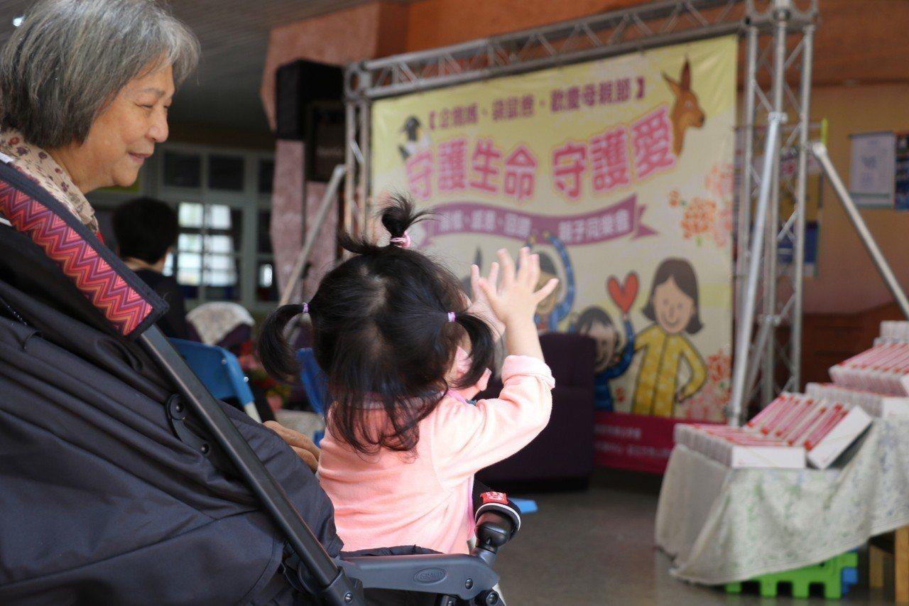 70歲的阿嬤帶著近2歲的小慈參加「企鵝爸、袋鼠媽圓夢感恩」活動,儘管小慈還不會奉...