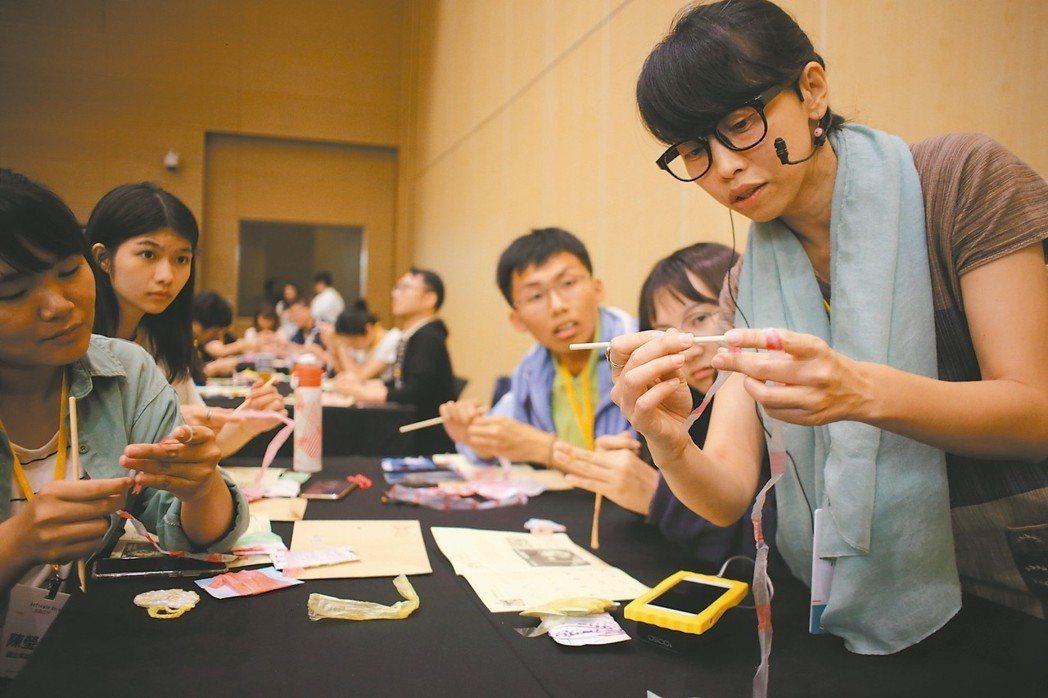 「廢青不廢」創辦人楊芳宜(右)帶領工作坊成員將手中的塑膠線做成藝品,具體實踐循環...