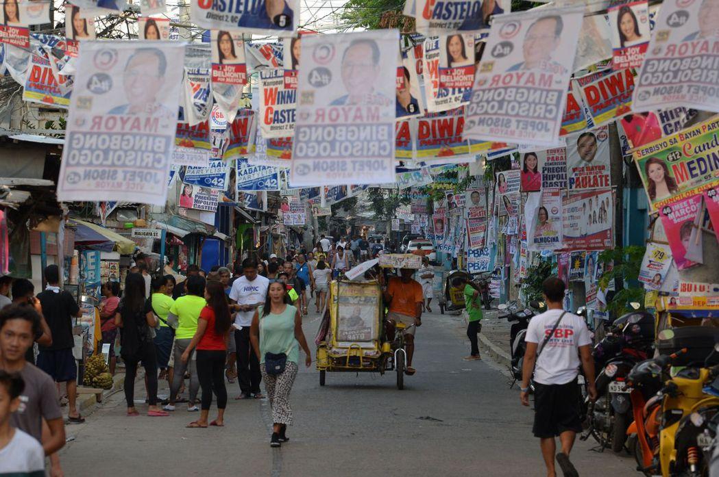 菲律賓期中選舉十三日投票,馬尼拉一處投票所附近街道投票日當天仍掛滿競選海報。 (...