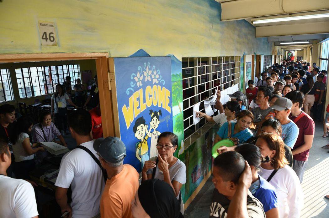 菲律賓十三日舉行期中選舉,民眾在馬尼拉一處投票所外排隊等待投票。 (法新社)