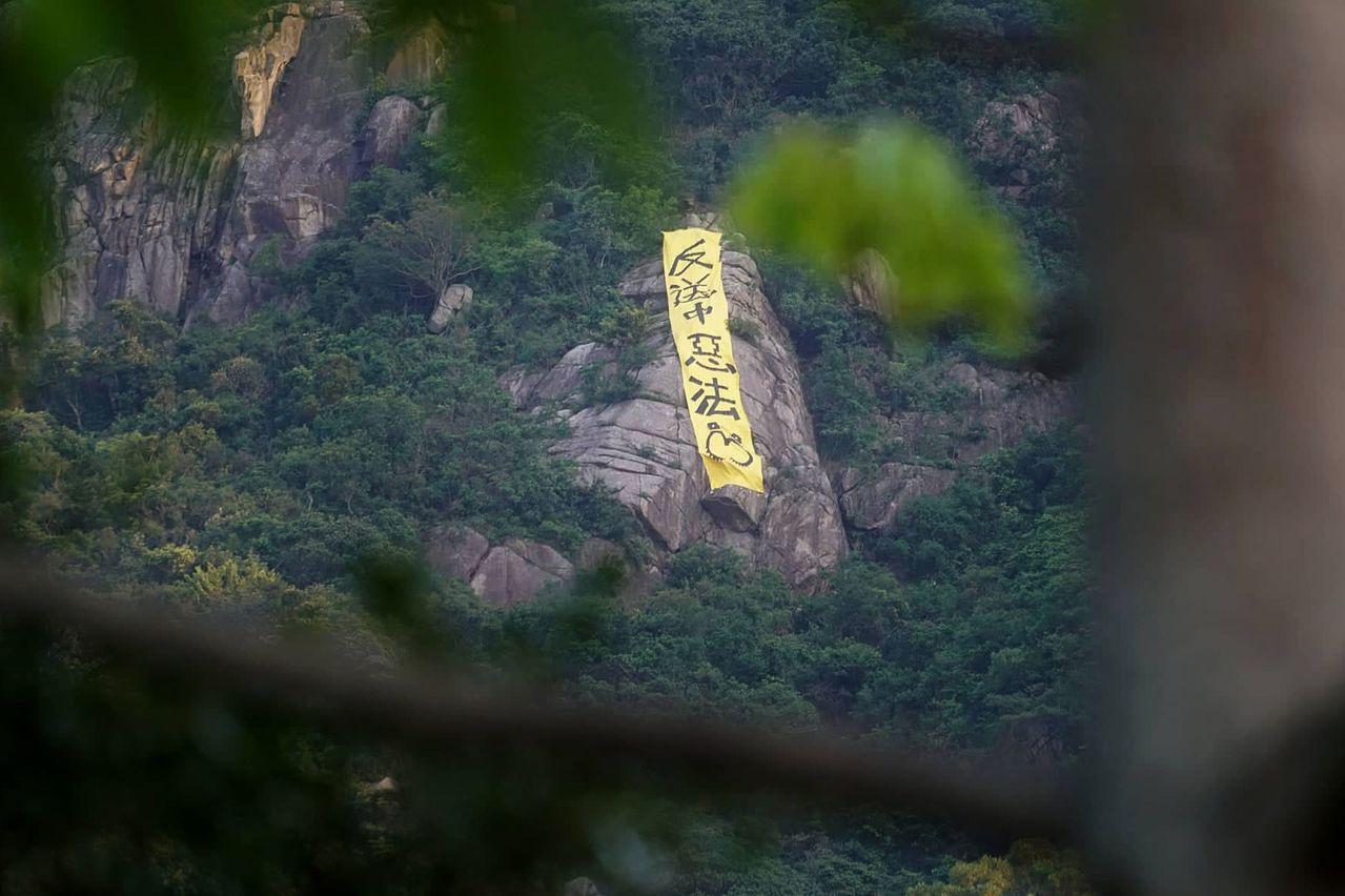 社民連昨晨於獅子山及畢架山山頭掛上「反送中惡法」黃色直幡布條,有市民見狀報警。 ...