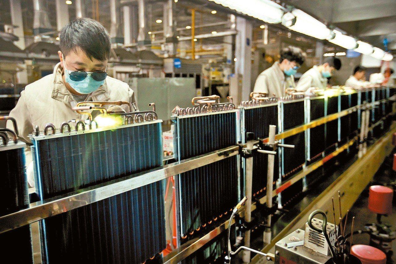 工廠工人在青島市附近工廠的裝配線上組裝產品。 美聯社