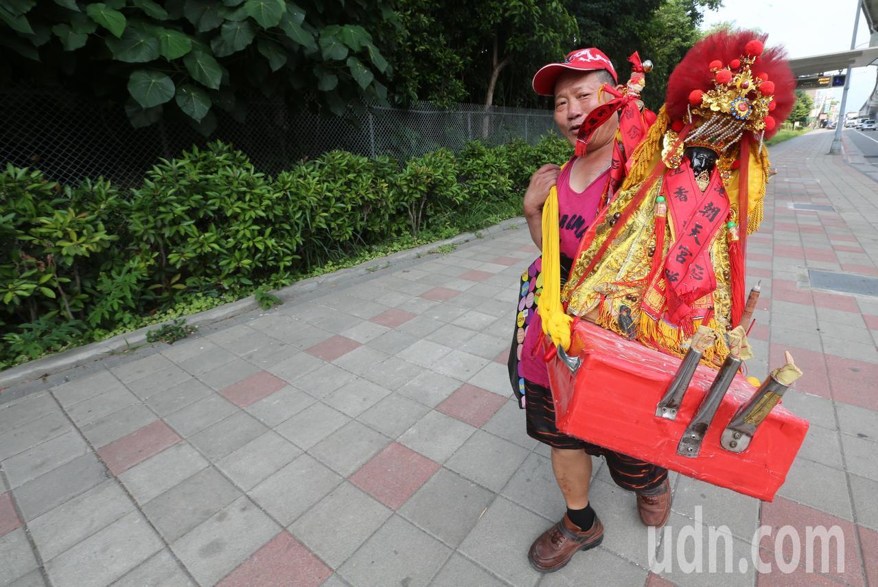 一個信徒背著他自己的媽祖神像,走在台北街頭「遶境」。記者胡經周/攝影