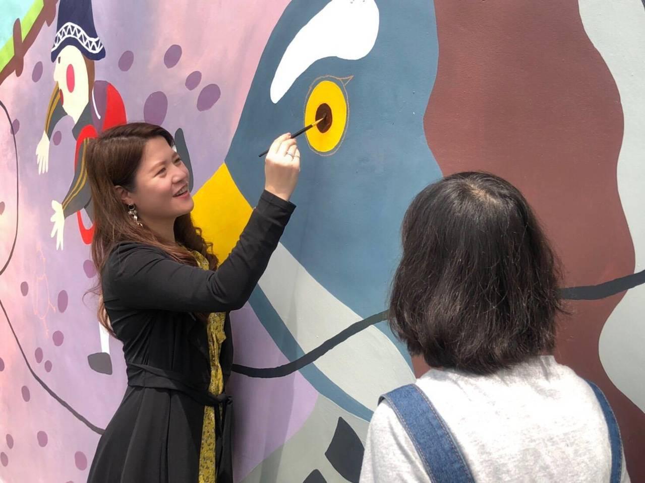 鐵砧山風景區的大型彩繪牆今天完工,台中市觀光旅遊局長林筱淇協助上色。圖/台中巿觀...