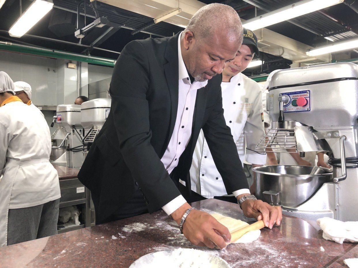 聖克里斯多福及尼維斯外交部長布蘭特利在開平餐飲學校烘焙教室體驗捏揉麵團,了解相關...