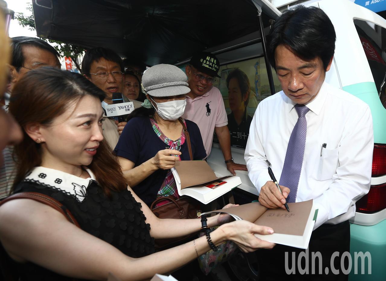 行政院前院長賴清德(右)前往逢甲夜市開講,演講結束後,有書迷拿書給他簽名。記者黃...