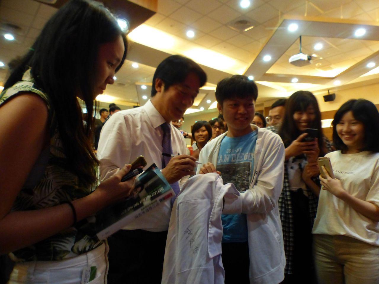 前行政院長賴清德(左二)今天下午應邀對中山醫學大學學生演講「醫學與人生」,學生爭...