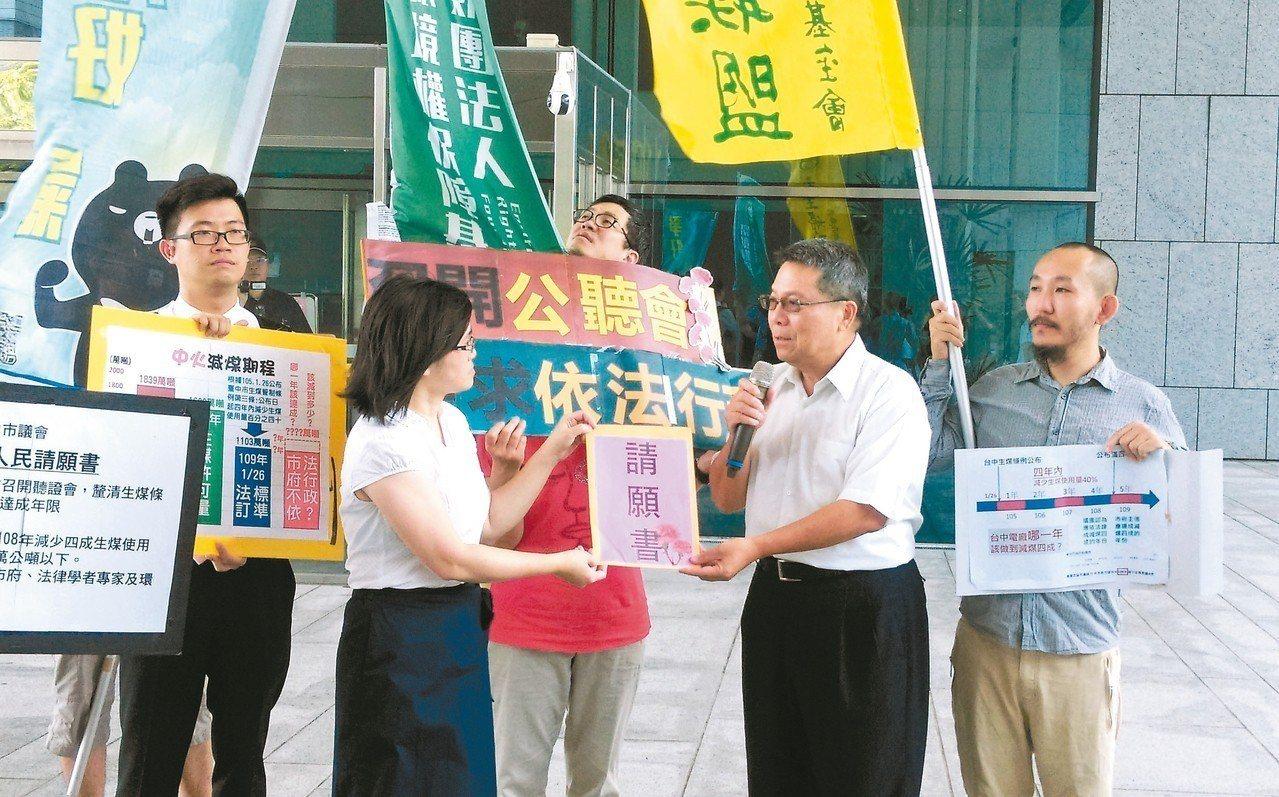 環團昨到中市議會前廣場提出請願並遞交請願書,由市議會秘書長張世禎(右二)接受。 ...