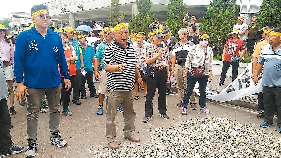 七股漁民昨在台南市政府前傾倒文蛤空殼,抗議太陽能光電業者要在七股魚塭種電。 記者...