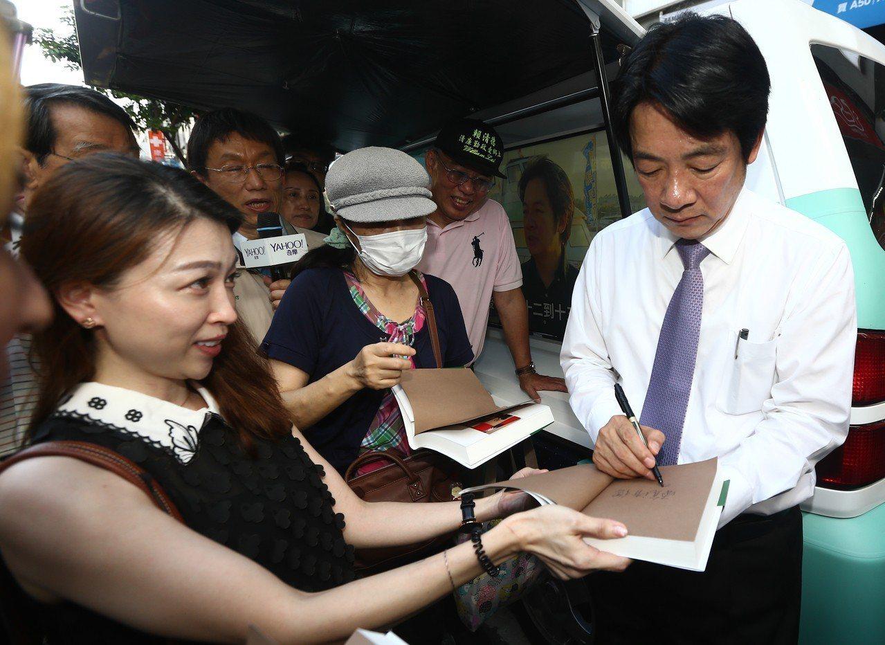 行政院前院長賴清德(右)昨天前往逢甲夜市開講,演講結束後,有書迷拿書給他簽名。 ...