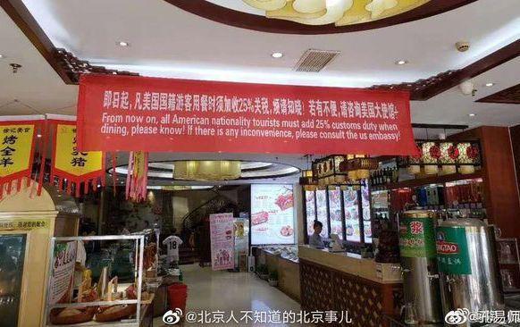 大陸一間餐廳外掛紅布條寫著「即日起,凡美國國籍遊客用餐時須加收25%關稅,煩請知...