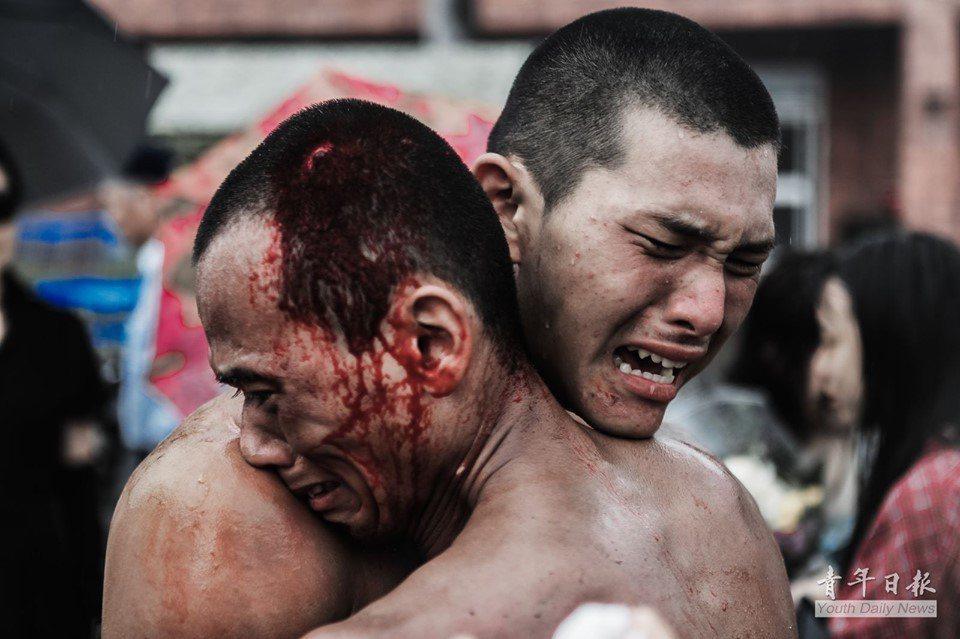 洪銘言中士頭部受傷,滿臉淌血爬完天堂路,與隊友相擁落淚。圖/國防部青年日報提供