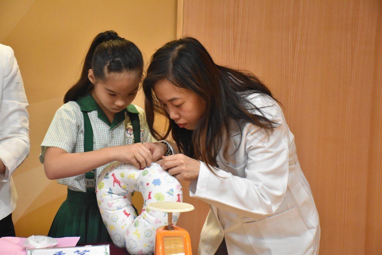 小朋友在中醫師的指導,將中藥材塞進U型枕裡面。記者江婉儀/攝影