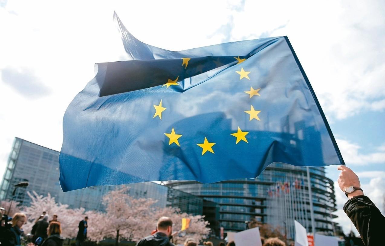 一名示威者在法國史特拉斯堡歐洲議會總部外揮舞歐盟旗。 (路透)
