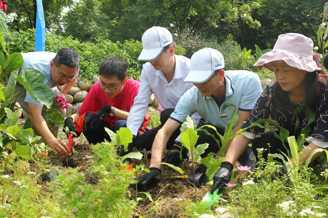 聯華電子總經理簡山傑(中)及新竹特殊教育學校師生們,在食物森林中學習種菜,友善環...