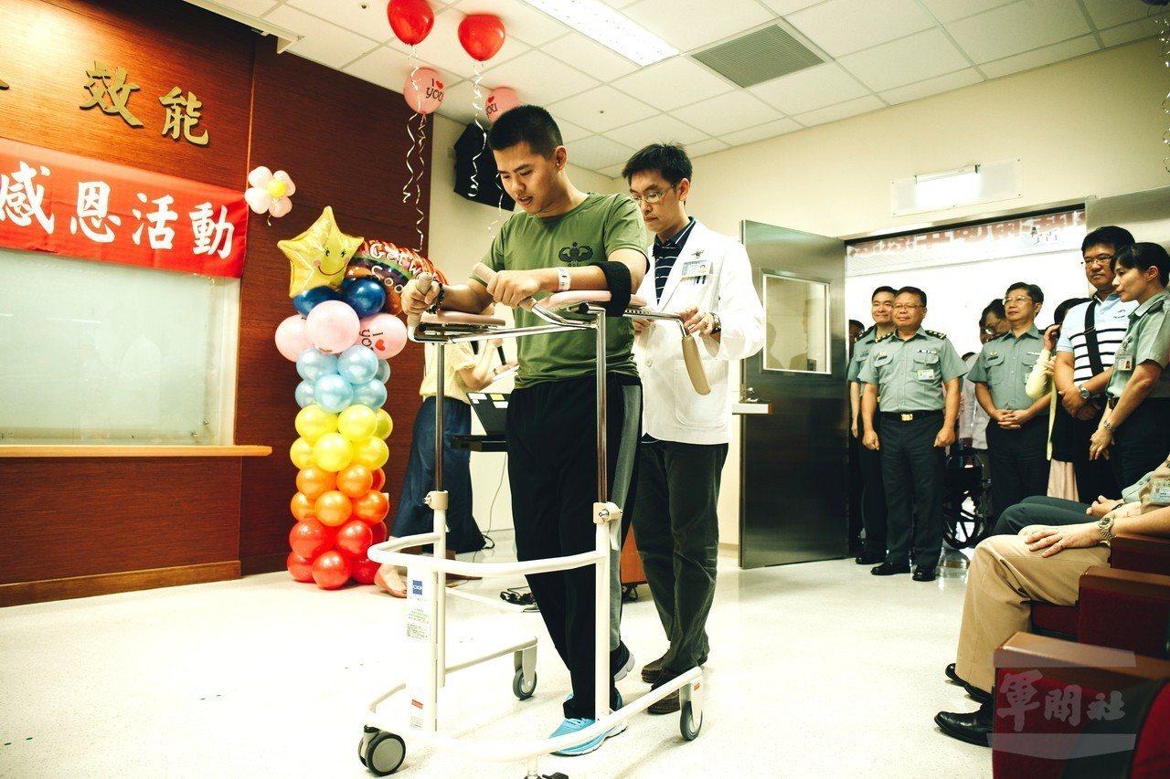 秦良丰撐著學步車練習走路,每次可以達兩分鐘以上。圖/軍聞社