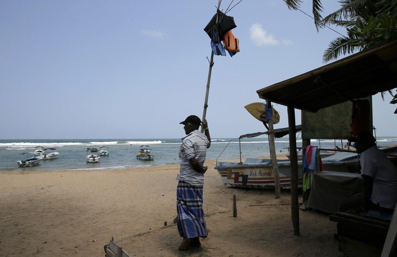 遊船業者獨自站在希卡杜瓦海灘,生意冷清。(美聯社)