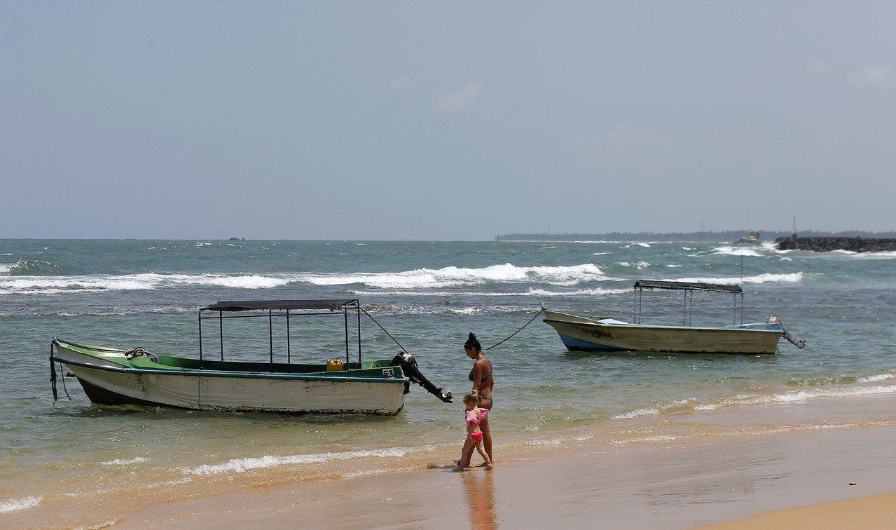 烏克蘭籍母子在空無一人的斯里蘭卡希卡杜瓦的海灘上漫步。(美聯社)
