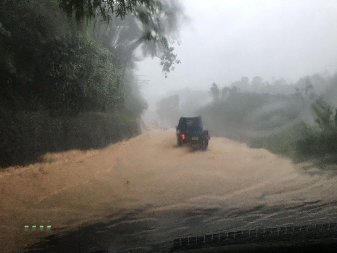 埔里鎮大坪頂上午洪水夾帶土石衝向路面,導致車輛受困,幸好驚險脫困。圖/泰雅渡假村...