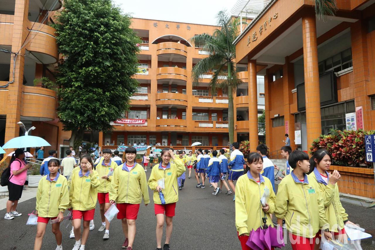 108國中會考首日,天氣不穩定時陰時晴,不少考生出考場沒帶傘,只好和同學擠一把傘...