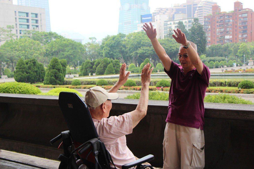 專門同陪長者就醫看診的照服員趙駿(右),喜歡在陪診服務後,陪著長輩們散步、聊天,...